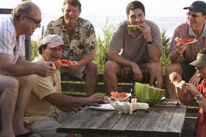 Group of friends eating watermelon outside.