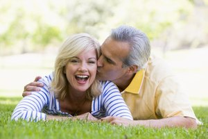 Husband kissing wife on grass