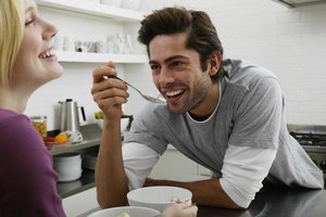A boyfriend and girlfriend laughing while eating in the kitchen.