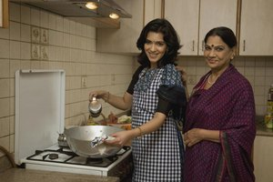 Two women cooking on the stove in a kitchen.