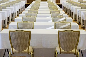 Rows of chairs and tables set up at an event.