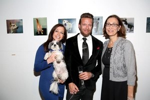 Attendees smiling at a fundraising party to benefit animals.