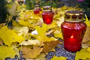 Red candle lanterns resting on a marble tombstone in a graveyard in the autumn.