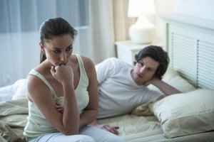 A young man looking at his tense girlfriend sitting on the edge of the bed.