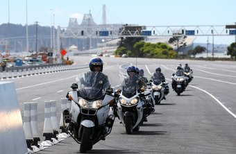 A fleet of CHP officers riding motorcycles on the freeway.