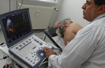 A vasular technologist looking at a monitor while conducting a sonogram.