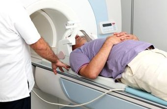 A patient receives an MRI with help from a Radiographer.