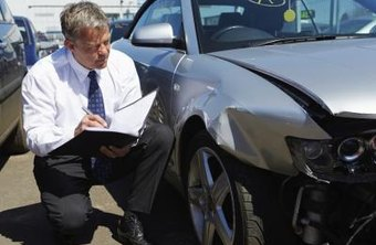 An insurance agent inspects a damaged car.