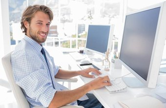A man sits at his computer workstation in a modern office.