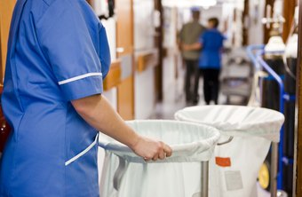 Hospital housekeepers collect used linens from patients' rooms.