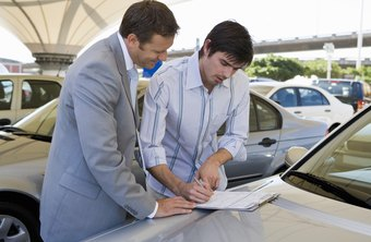 A car salesman negotiates prices to potential car buyers.