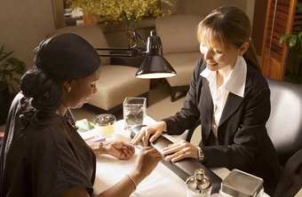 A manicurist spends much time sitting while working on a client's nails.