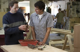 A carpenter apprentice learns the trade from experienced carpenters.