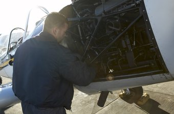 Aircraft maintenance engineers inspect plane engines for problems.