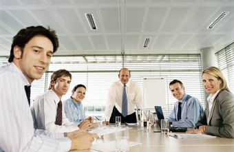 In a boardroom meeting, one person takes the meeting's minutes.