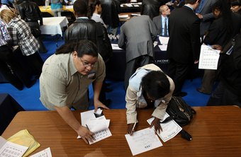 Organize and complete applications at an empty table at the job fair.