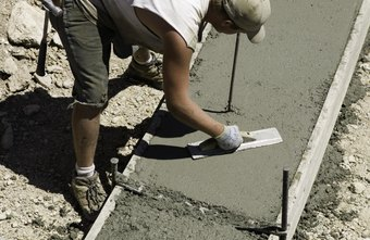 Concrete finishers smooth surfaces with trowels.
