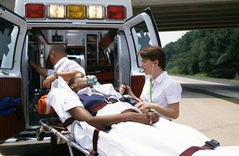 Paramedics administer treatment before placing patients in ambulances.