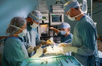 The scrub nurse passes forceps, scalpels and other instruments to surgeons as needed.