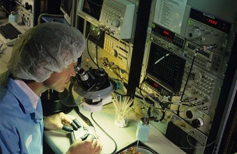 Computer science engineers examine chip quality with a microscope.