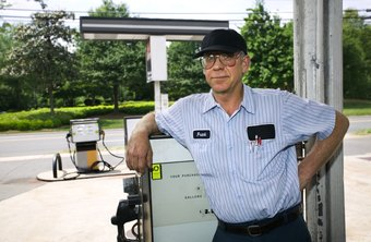 An assistant manager at a gas station monitors the condition of gas pumps.