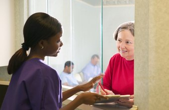 A clinic receptionist greets patients and handles check-ins.