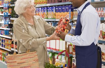 Retail workers help customers with their purchases.