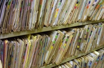 Medical records specialists keep hard copies in a filing system.