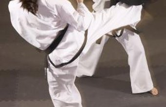 Taekwondo students kick pads to develop explosive strength.