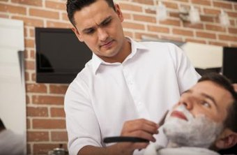 A barber shaves a clients face.