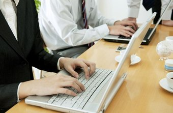 Close-up of businesswoman typing email up on laptop in office.