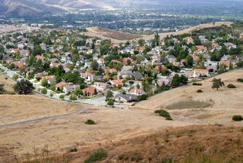 Urban sprawl results in housing developments pressed up against wilderness.