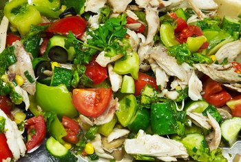 For a colorful, delicious packed lunch, create a salad topped with chunks of chicken.