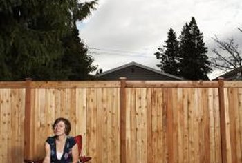 Harsh wooden fence lines need softening from landscaping.