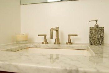 Cultured-marble vanity tops are typically glued to the underlying surface with silicone or acrylic adhesive.