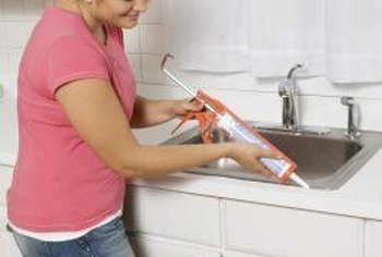Kitchen and bathroom sinks are adhered with silicone caulk to fasten the  sink and create a