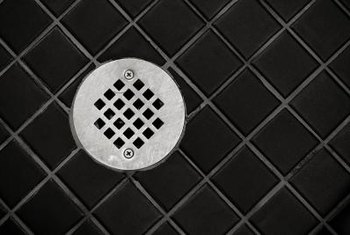 Tiles must be cut around shower drains.