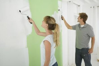 This couple is cooperating to paint an interior wall.