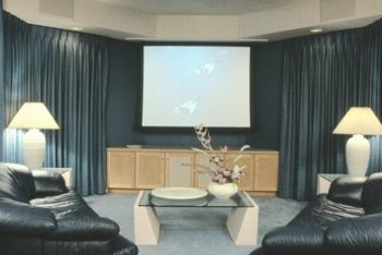 Dark walls, blackout draperies and comfortable seating enhance a home theater.