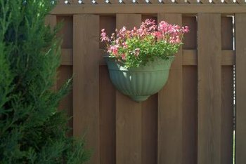 Add flower baskets to privacy fences to soften outdoor spaces.
