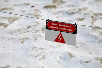Install electric fence warning signs on each side to warn people not to touch the wires.