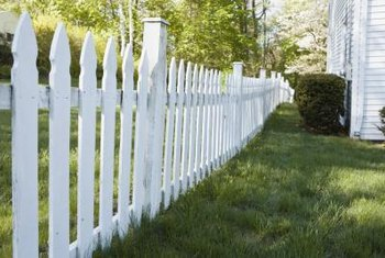 Edging along a picket fence prevents grass, weeds and garden plants from spreading under the fence.