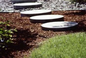 A combination of concrete stepping pavers and gravel makes an easy walkway in a garden.