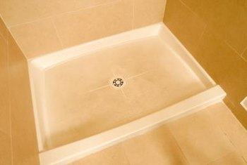 Periodic maintenance includes cleaning a fiberglass shower pan.