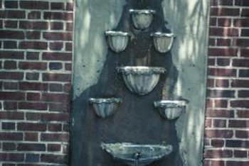 A wall fountain works well in a small yard or garden because it doesn't require as much space.