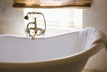 A clawfoot tub faucet with a classic telephone-style hand shower.