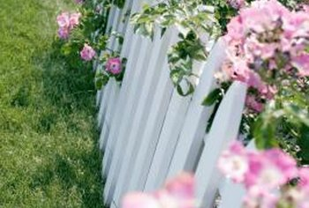 Adorning a picket fence with flowers makes an attractive lawn divider.