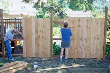 Setting the posts is the first step in installing wood panel fencing.