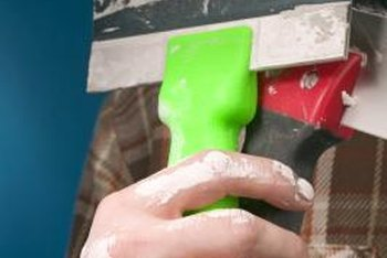 A sturdy putty knife is a must-have tool when pulling up self-stick tile.