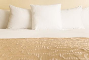 Solid color matelasse bedspreads pair with matching, ruffled bedskirts.